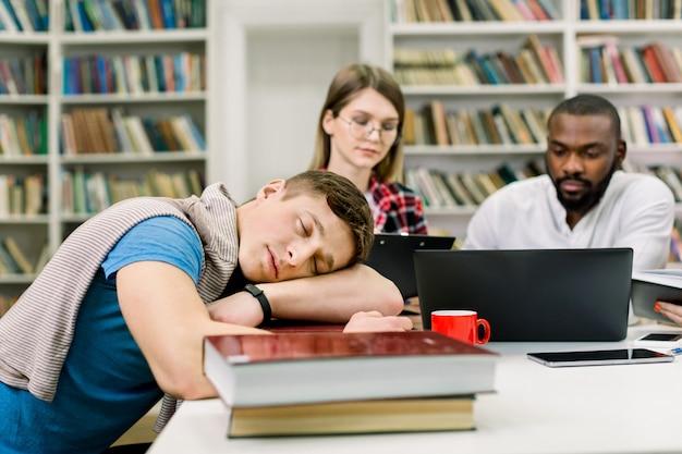 Müder schlafender hübscher männlicher student, der auf seinen händen und büchern auf tisch liegt. konzentrierte multiethnische studenten, die sich auf prüfungen vorbereiten