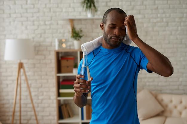 Müder schwarzer mann wischt sich nach dem training den schweiß vom gesicht