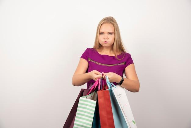 Müder shopaholic, der bunte einkaufstaschen hält.