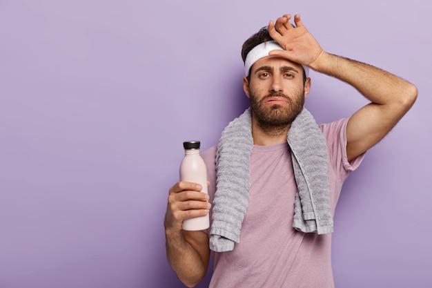 Müder sportler seufzt vor müdigkeit, wischt sich den schweiß von der stirn, trinkt kaltes wasser, benutzt ein handtuch und trainiert aktiv cardio