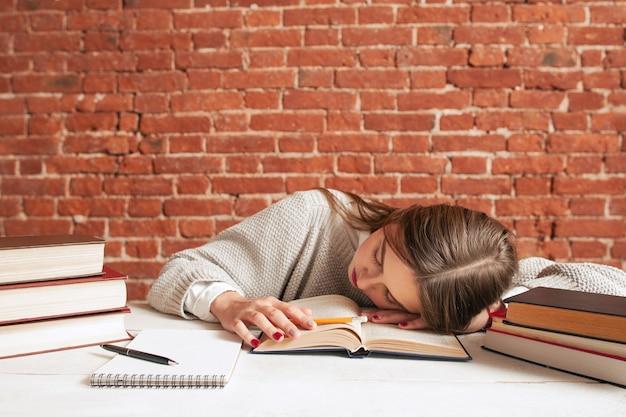 Müder student, der auf buch in der bibliothek schläft