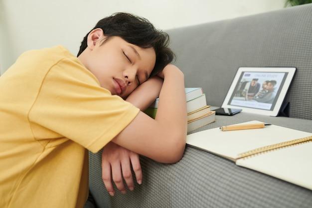 Müder teenager, der zwischen online-kursen auf bücherstapel schläft