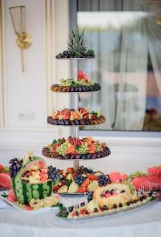 Müder teller mit geschnittenen pflaumen, traube, ananas und anderen früchten