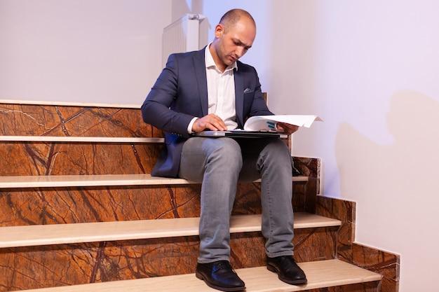Müder überarbeiteter geschäftsmann, der spät in der nacht an der projektfrist arbeitet. unternehmer, der spät abends arbeitet, sitzt auf der treppe im baubüro.
