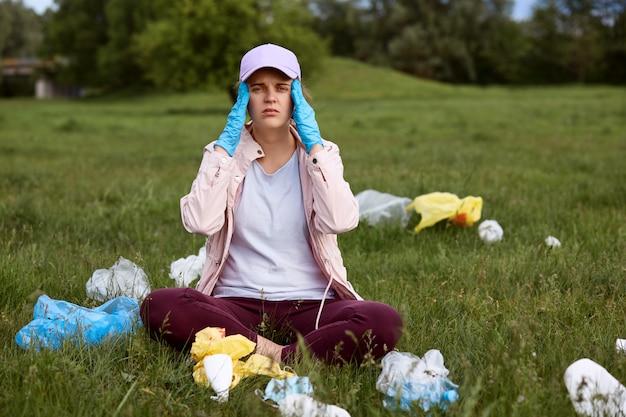 Müder umweltaktivist, der auf grünem gras mit den fingern an den schläfen sitzt