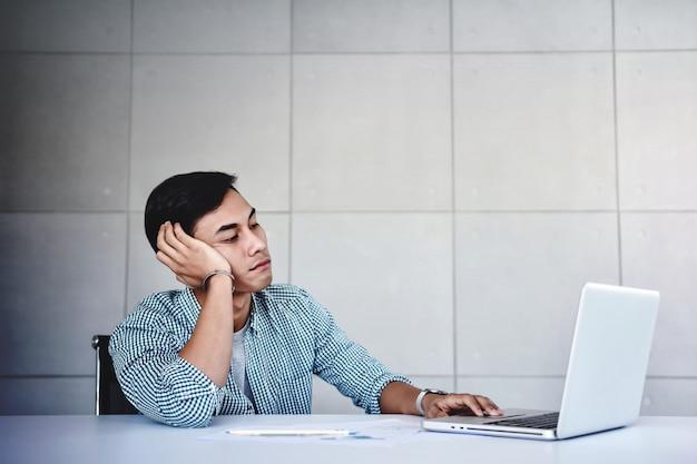 Müder und betonter junger geschäftsmann sitting auf schreibtisch im büro mit computer