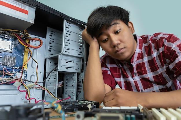 Müder und gelangweilter computer-mechaniker sitzt an seinem arbeitsplatz und denkt nach.