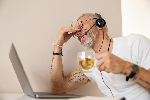 Müder unternehmer, der sich nach der arbeit mit laptop die nase reibt