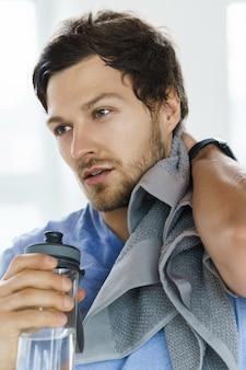Müder verschwitzter mann mit handtuch nach dem fitnesstraining im fitnessstudio