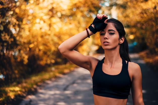 Müder weiblicher läufer, der eine pause macht.