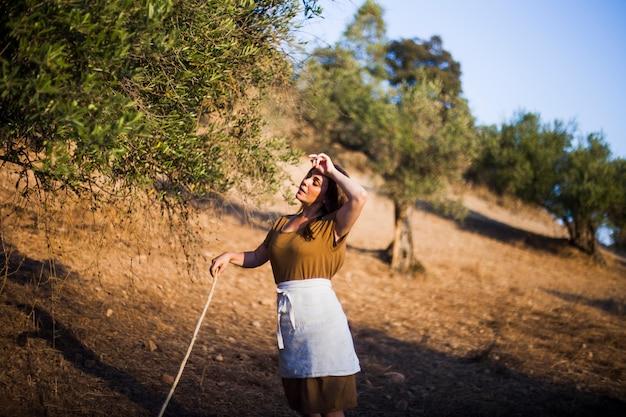 Müder weiblicher landwirt auf einem gebiet der olivgrünen obstgärten