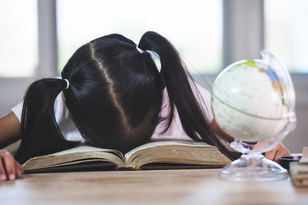 Müdes asiatisches mädchen des kleinen kindes, das über dem geöffneten buch im klassenzimmer schläft