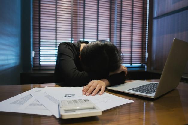 Müdes geschäftsfrauschlafen / ein schläfchen halten in einem büro mit laptop und finanzdokumenten