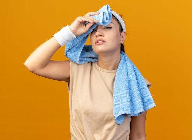 Müdes junges, kaukasisches, sportliches mädchen mit stirnband und armbändern mit handtuch um den hals, das die stirn mit dem handtuch isoliert auf der orangefarbenen wand abwischt