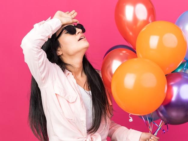 Müdes junges schönes mädchen mit brille, das ballons hält und hand auf die stirn legt