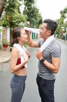 Müdes junges vietnamesisches paar, das sich nach dem gemeinsamen training im freien den schweiß abwischt