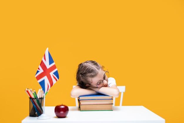 Müdes kaukasisches schulmädchen, das am schreibtisch sitzt und englischunterricht schläft großbritannien flagge