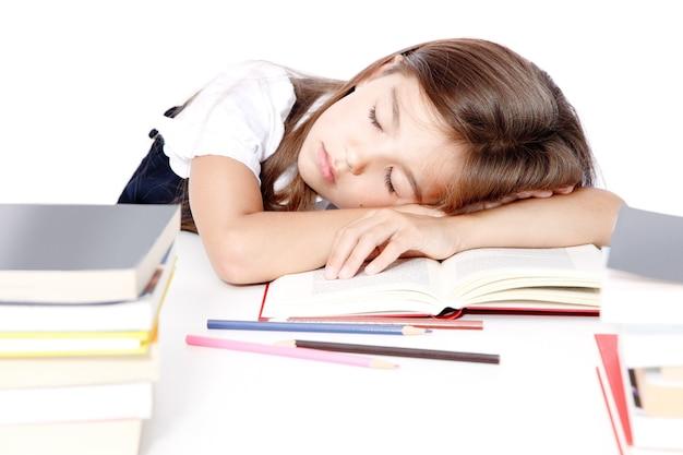 Müdes kleines mädchen, das in der schule auf dem schreibtisch schläft.