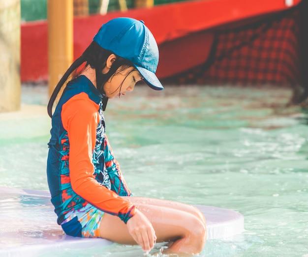 Müdes kleines mädchen sitzt im schwimmenden trainingspool