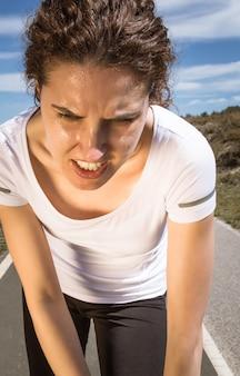 Müdes läufermädchen, das nach dem laufen mit sonne schwitzt