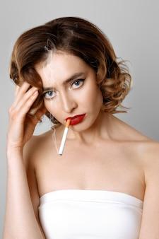 Müdes schönheitsmodell mit rauchender sigarette der kopfschmerzen