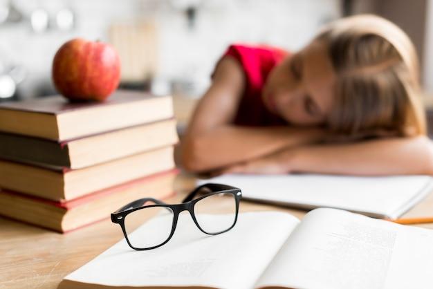 Müdes schulmädchen, das am schreibtisch schläft