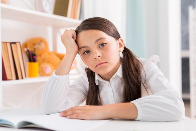 Müdes schulmädchen, das hausarbeit am schreibtisch tut