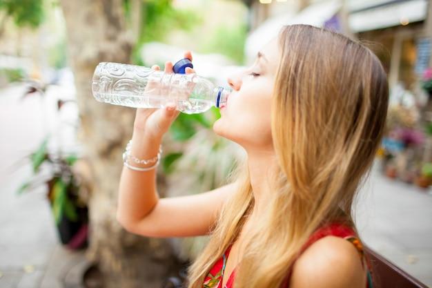 Müdes trinkwasser des weiblichen touristen draußen