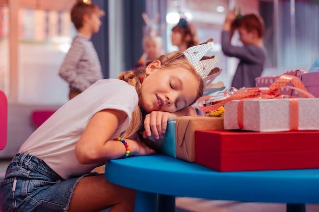 Müdigkeit fühlen. charmantes blondes kind, das die augen geschlossen hält, während es während der feier schläft