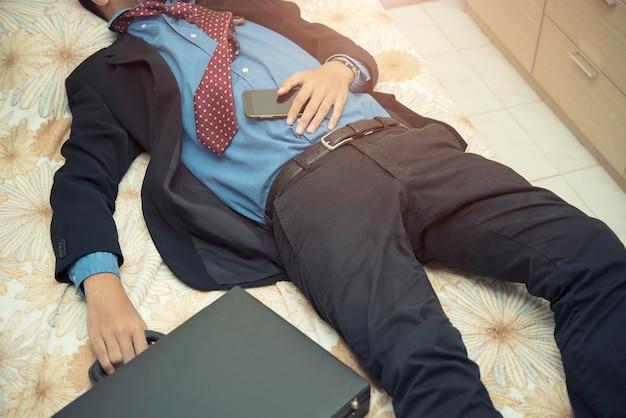 Müdigkeitsgeschäftsmann, der in der klage mit tasche und mobile schläft