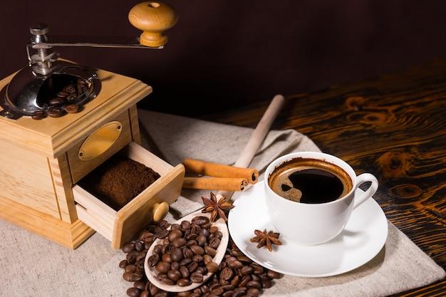 Mühle mit frisch gemahlenem kaffee neben bohnen