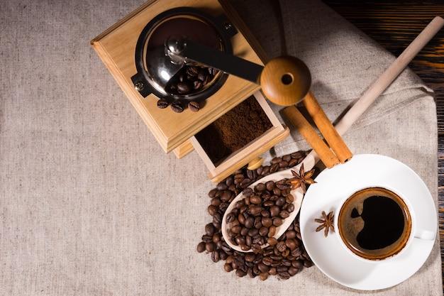 Mühle mit kaffeebohnen und holzlöffel neben becher mit sternanis und zimtstangen auf leinwand verziert