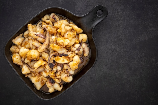 Muek tod kra-tiam prik-thai, thailändisches essen, gebratene tintenfische mit knoblauch und pfeffer in schwarzer pfanne auf dunklem texturhintergrund mit kopierraum für text