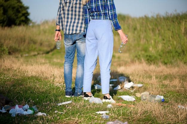 Müll am strand. junges paar, das am strand neben einem haufen müll ruht. mensch- und naturkonzept
