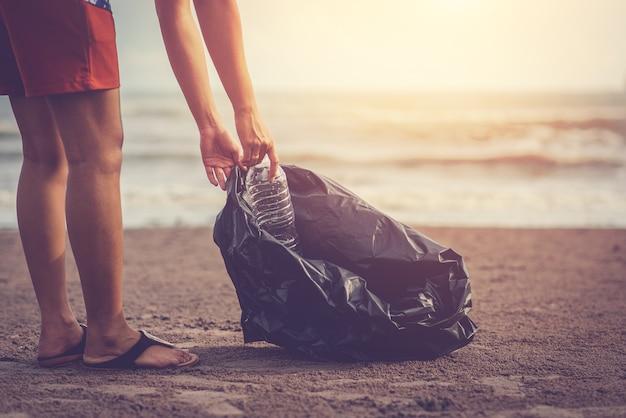 Müll am strand mit dem hintergrund des lichtes der sonne sammeln / das meer lieben