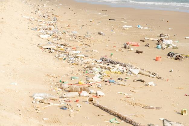 Müll am tropischen strand. umweltproblem durch plastikverschmutzung. plastikflaschen und anderer müll wurden am strand angespült.