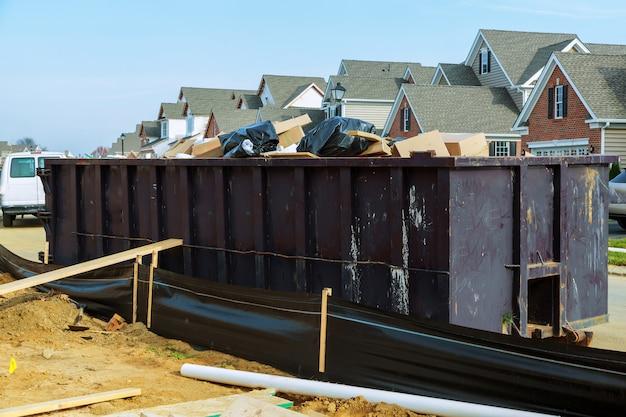 Müllcontainer, die mit abfall in einer stadt voll sind.