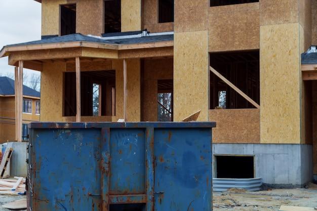 Müllcontainer, papierkorb und mülltonnen in der nähe der neuen baustelle der wohnhäuser bauen