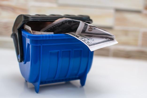 Mülleimer blau, dollarpakete auf hellem hintergrund