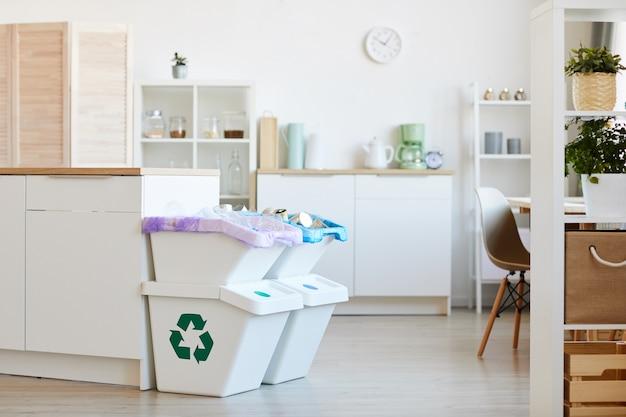 Mülleimer stehen in der nähe des küchentischs zu hause
