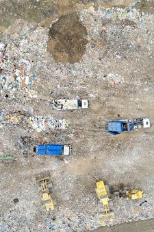 Müllhaufen in müllkippe oder mülldeponie. muldenkipper und bagger entladen abfälle.