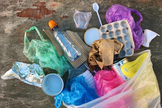 Müllsack mit verschiedenem müll auf hölzernem hintergrund. draufsicht. flach liegen.