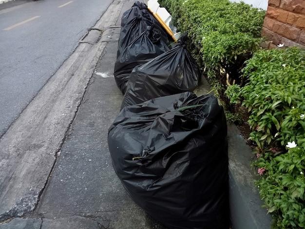 Müllsäcke, schwarze müllsäcke, auf dem fußweg. umwelt- und objektkonzept.