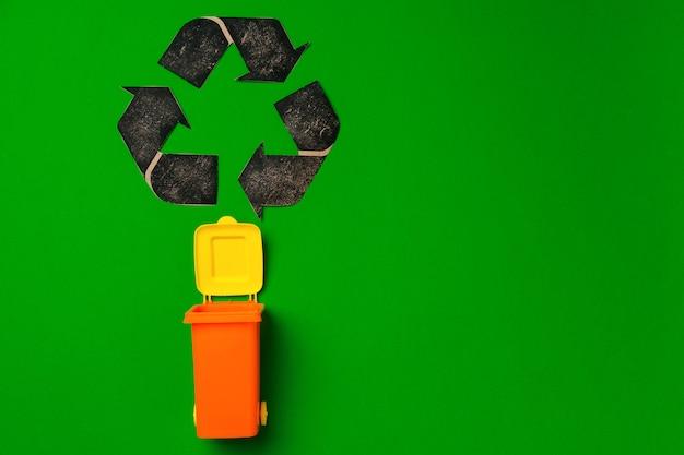 Müllsortierungskonzept mit spielzeugabfallbehälter auf papierhintergrund