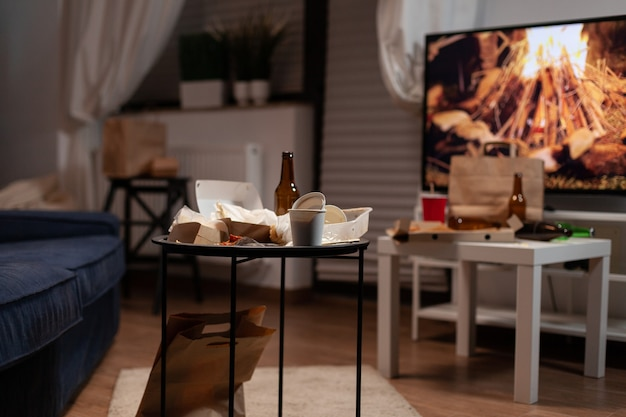 Mülltisch mit leerer bierflasche und essensabfällen im wohnzimmer