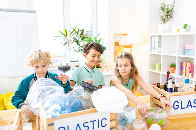 Mülltrennung studieren. intelligente strahlende kinder, die im ökologieunterricht in der schule mülltrennung studieren studying