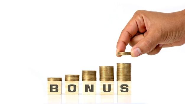 Münz- und münzzeiger auf quadratischem holzblock mit bonusnachricht. geld- und vergütungskonzept.