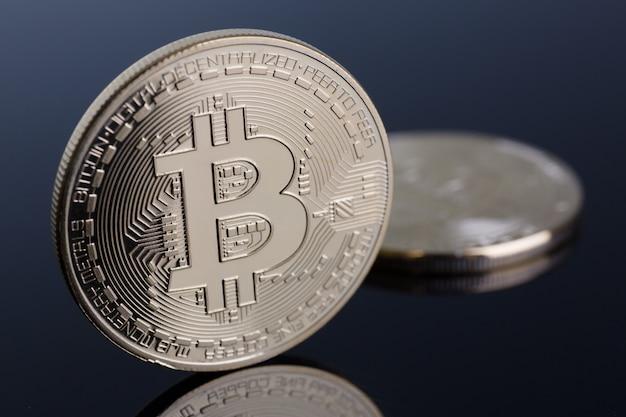 Münze der kryptowährung bitcoin auf einem grau-blauen hintergrund mit reflexionsgegenstand-goldaustauschpyramide auf geld im zusammenhang mit der wachstums- oder fallwechselkursnahaufnahme.
