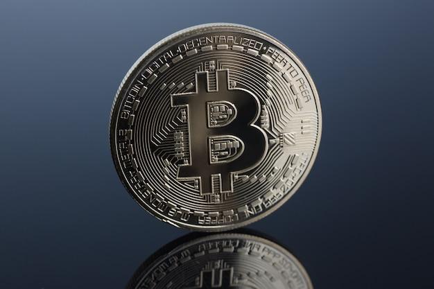 Münze der kryptowährung bitcoin auf einem grau-blauen