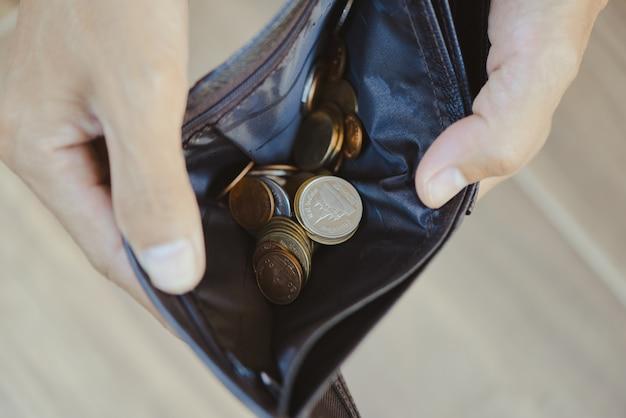 Münze im brieftaschen- und schuldenmanagementkonzept. leere brieftasche in den händen eines älteren mannes armut im ruhestandskonzept